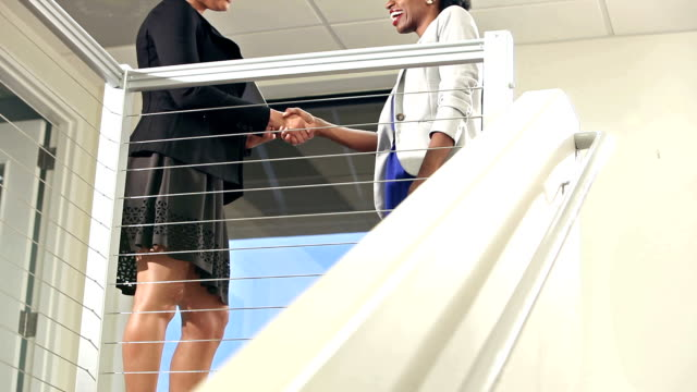 Businesswoman climbs stairs, shakes hands with colleague video