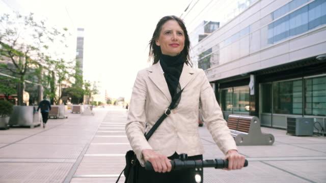 businesswoman commuting on electric scooter - monopattino elettrico video stock e b–roll