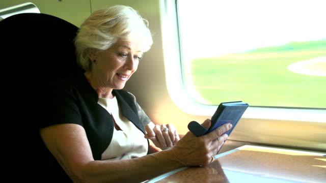 vídeos de stock e filmes b-roll de mulher de negócios a viagem de casa para o trabalho no comboio e livro de leitura - senior business woman tablet