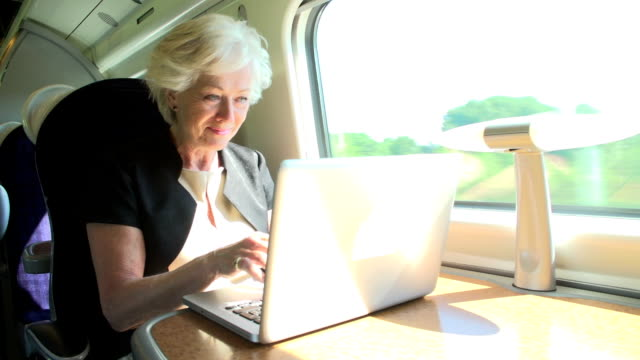 Businesswoman Commuting To Work On Train And Using Laptop video