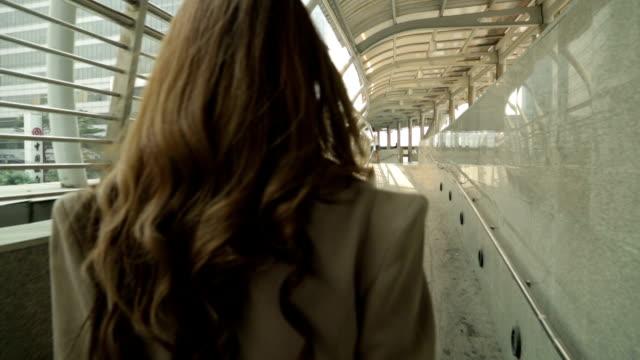 biznesmenka zaufanie chodzić w skywalk - podążać za czynność ruchowa filmów i materiałów b-roll