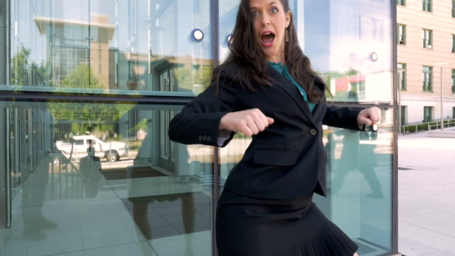 a businesswoman crazy dancing celebrating her success outside office building - trentenne video stock e b–roll