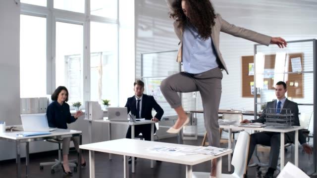 vidéos et rushes de femme d'affaires dansant sur la table dans le bureau avec des collègues gais - lancer