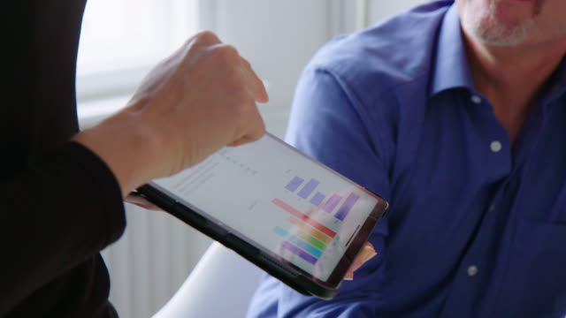 Businesswoman discussing market research data in meeting Close-up of a woman pointing and explaining statistical graph over digital tablet to male colleague in office. Businesswoman discussing market research data with team in meeting. explaining stock videos & royalty-free footage