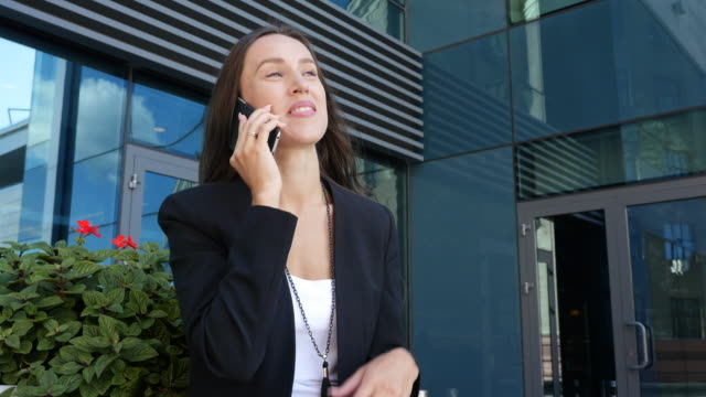 Businesswoman discussing on a cell phone details with a client, pan shot video