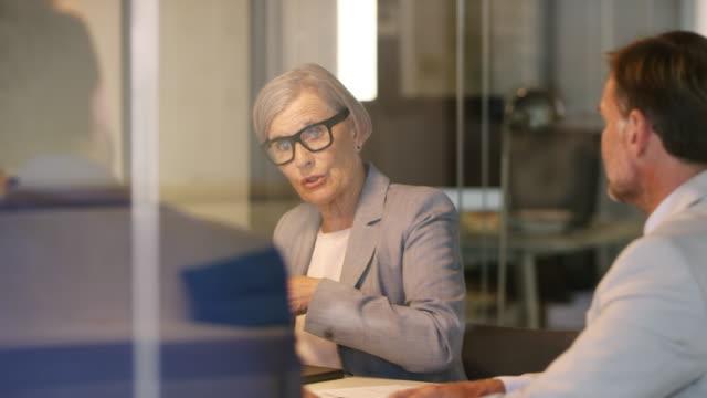 affärskvinna som diskuterar strategi med kolleger - endast vuxna bildbanksvideor och videomaterial från bakom kulisserna