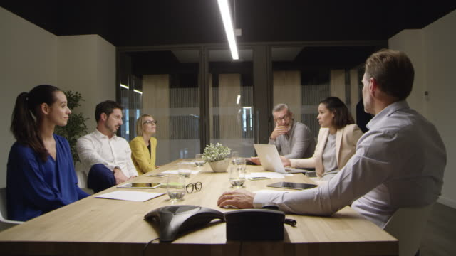Businesswoman discussing with colleagues at table