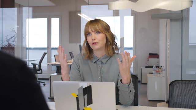 Businesswoman discussing with coworker in office