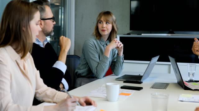 affärskvinna som diskuterar med medarbetare i mötet - office workers talking bildbanksvideor och videomaterial från bakom kulisserna