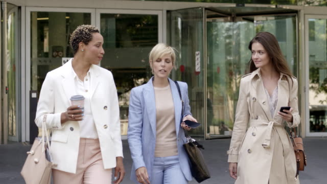 Businesswoman discussing with female colleagues Mature businesswoman discussing with female colleagues in city. Confident coworkers are talking while walking in downtown. They are in smart casuals. mid adult stock videos & royalty-free footage