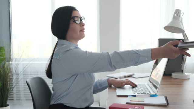 Businesswoman doing paperwork and using laptop at office