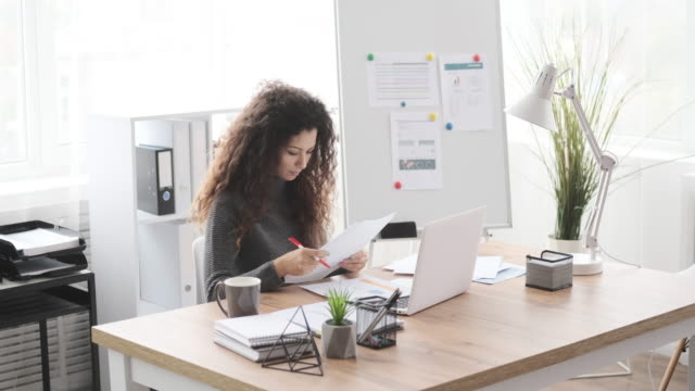 Businesswoman doing paperwork and writing notes at office