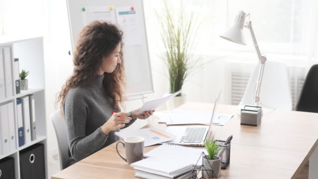 Businesswoman doing paperwork at office