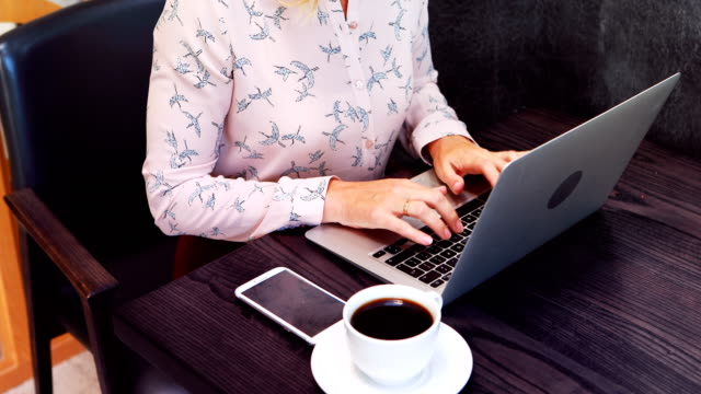 Businesswoman drink coffee while working on laptop video