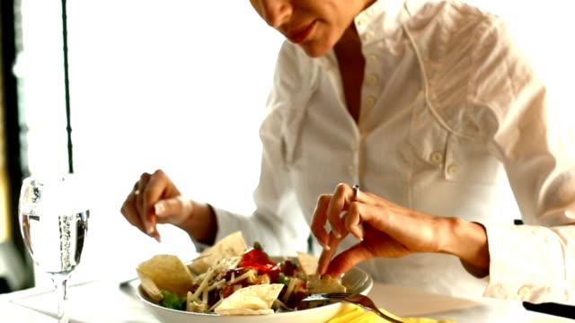 Businesswoman eating in restaurant. video