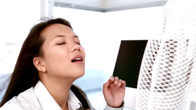 Businesswoman enjoying cool air from the fan video