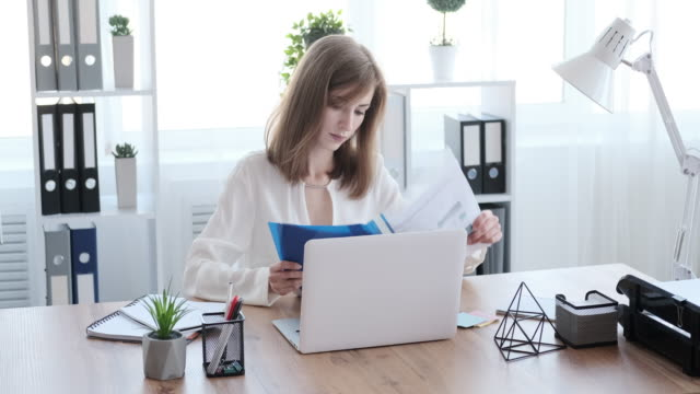 Businesswoman examining documents and writing notes at office