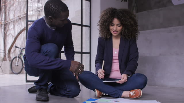 Businesswoman explaining documents to colleague video