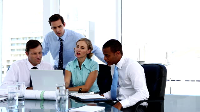 Businesswoman explaining something to her colleagues while using a laptop video