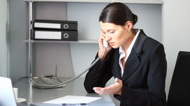 Businesswoman getting bad news by the phone. Young businesswoman getting bad news by the phone. landline phone stock videos & royalty-free footage