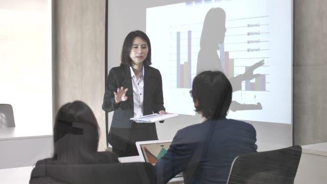 実業家は、彼女のビジネス部門の同僚と会議室でマネージャーのプレゼンテーションを与える - ビジネスウーマン点の映像素材/bロール