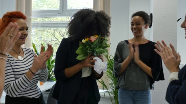 vidéos et rushes de femme d'affaires donnant bouquet au collègue souriant - composition florale