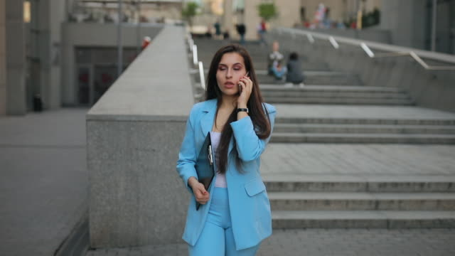 geschäftsfrau geht nach der arbeit nach hause und telefoniert - formelle geschäftskleidung stock-videos und b-roll-filmmaterial