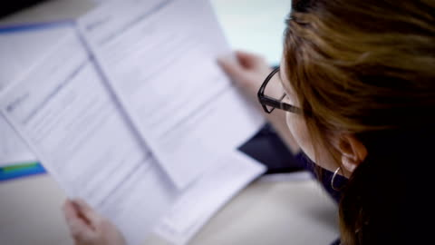 Businesswoman goes through documents very carefully Businesswoman verifies documents in the office sitting at the table. She is reading carefully page by page. agreement stock videos & royalty-free footage