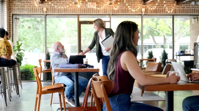 Businesswoman greets male colleague in coffee shop Confident Caucasian businesswoman walks into a coffee shop and shakes a male colleague's hand in greeting. She sits down at the table with her colleague as they begin their meeting. mid adult stock videos & royalty-free footage