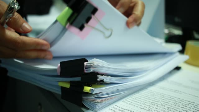Businesswoman hands working on Stacks of documents files for finance in office. Business report papers or Piles of unfinished document achieves with black clip paper. Concept of Business Annual Report video