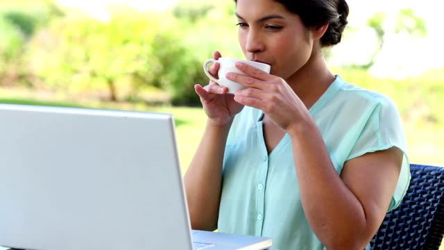 コーヒーを持つビジネスウーマンワーキングにノートパソコン - ソーサー点の映像素材/bロール