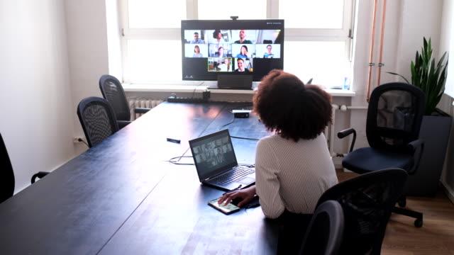 vidéos et rushes de femme d'affaires ayant la conférence web avec des collègues - conférence en ligne