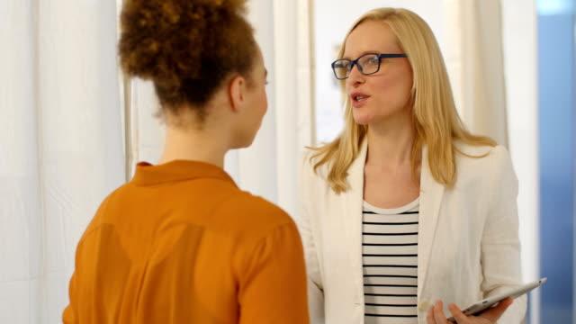 Mujer de negocios de retención de tableta digital mientras habla con colega - vídeo