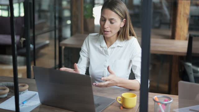 Businesswoman in a video conference, using laptop Businesswoman working in a glass isolated area, having a video call businesswear stock videos & royalty-free footage