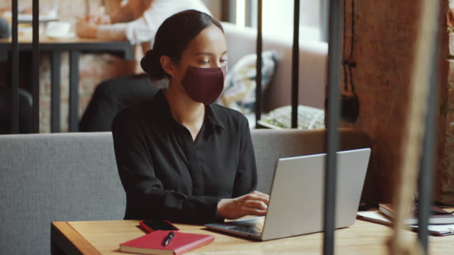 vídeos de stock e filmes b-roll de businesswoman in face mask typing on laptop in cafe - remote work