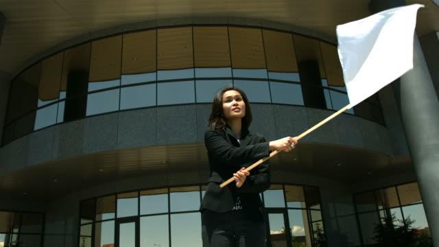 donna d'affari davanti edificio per uffici di bandiera bianca - molla video stock e b–roll