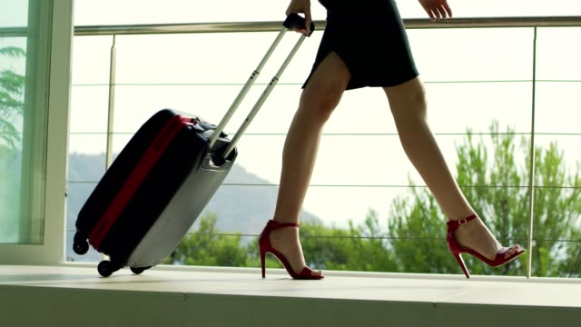 Businesswoman in red highheels arriving to airport.