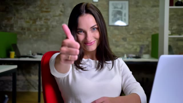 businesswoman in the office watches to the camera and puts her finger up to show the like and respect - congratulations stock videos & royalty-free footage