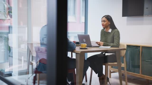 vídeos y material grabado en eventos de stock de mujer empresaria entrevistando al candidato masculino del trabajo en la sala de reuniones - dos personas