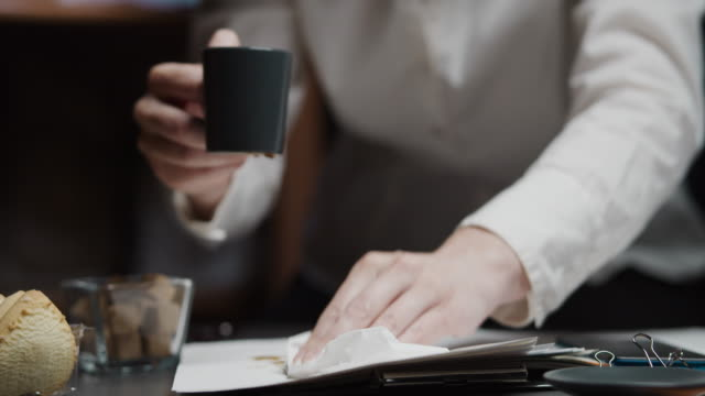 Businesswoman is overflowing coffee during paper work video