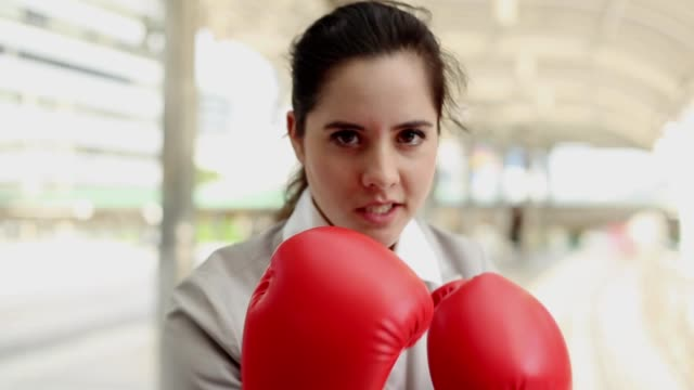 businesswoman keeps punching and raising hands with red boxing gloves - stalowy filmów i materiałów b-roll