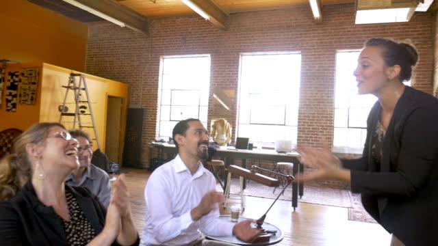 vídeos de stock e filmes b-roll de businesswoman leads a presentation at motivational event with clapping - orador público