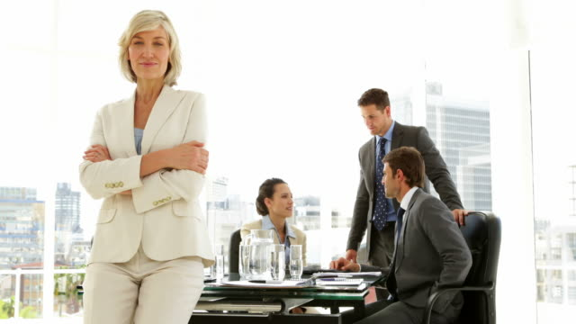 Businesswoman leaning on desk with team behind her video