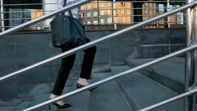 Businesswoman Legs In High-Heeled Shoes Walking Up Stairs On Stairway