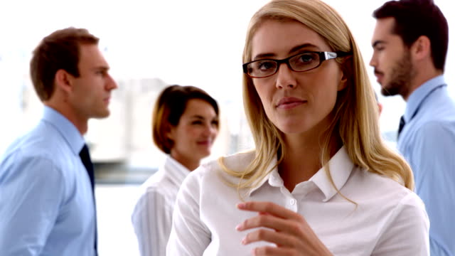 Businesswoman looking at camera with colleagues behind her video