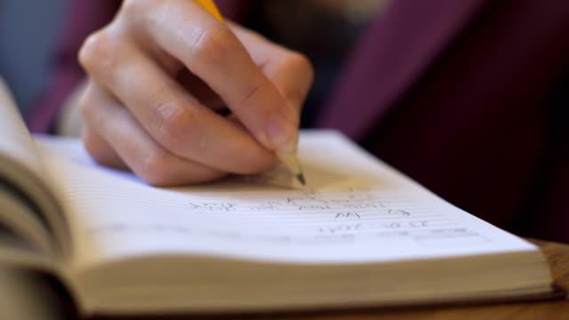 affärskvinna gör anteckningar i en anteckningsbok i coffee shop. - anteckningsblock bildbanksvideor och videomaterial från bakom kulisserna