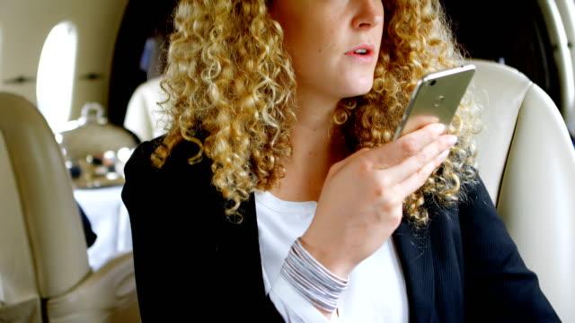geschäftsfrau auf einen anruf im privat-jet 4k - gefreiter stock-videos und b-roll-filmmaterial