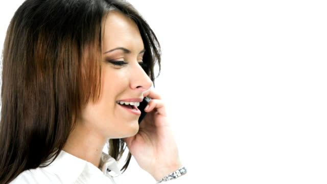 Businesswoman on cellphone, looking at camera and smiling, over white video