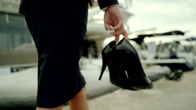 businesswoman on vacation. walking barefoot on marina - high heels stock videos & royalty-free footage