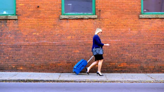 Businesswoman pulling suitcase down sidewalk in city. video